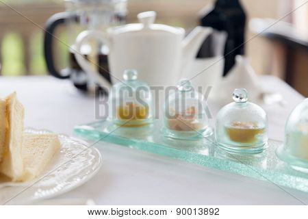 food, breakfast and eating concept - close up of tea time set with jam on table at restaurant