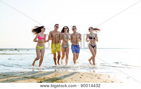 friendship, sea, summer vacation, holidays and people concept - group of smiling friends wearing swimwear and sunglasses running on beach