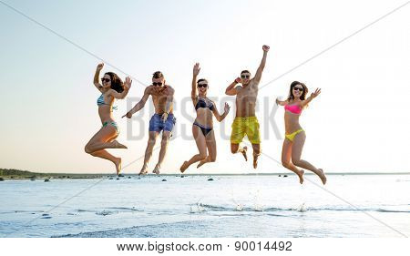 friendship, sea, summer vacation, holidays and people concept - group of smiling friends wearing swimwear and sunglasses jumping on beach