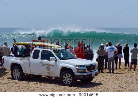 Spectators And Lifeguards Observing Huge Surf