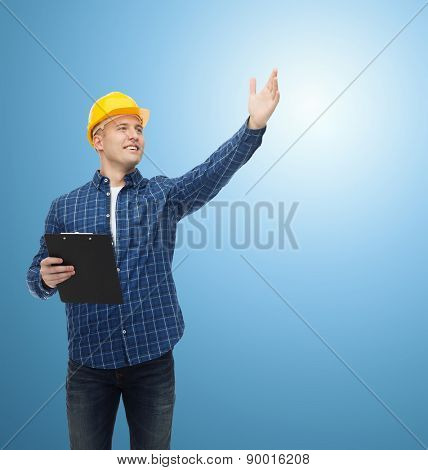 repair, construction, building, people and maintenance concept - smiling male builder or manual worker in helmet with clipboard pointing hand over blue background