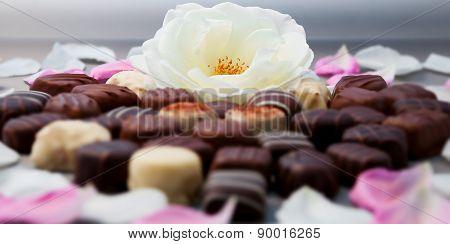 Romantic chocolate truffles and white roses heart shape setup horizontal