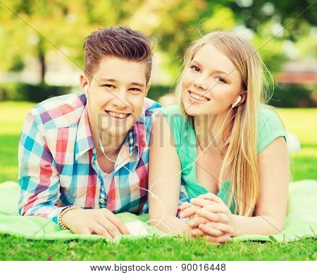 vacation, holidays, technology and friendship concept - smiling couple with smartphone and earphones lying on blanket in park