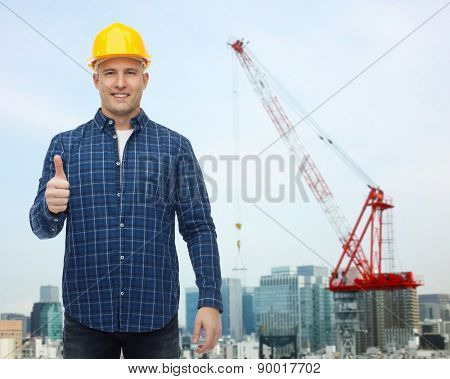 repair, construction, building, people and maintenance concept - smiling male builder or manual worker in helmet showing thumbs up over city construction site background