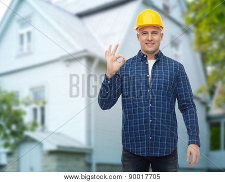 repair, construction, building, people and maintenance concept - smiling male builder or manual worker in helmet showing ok sign over living house background