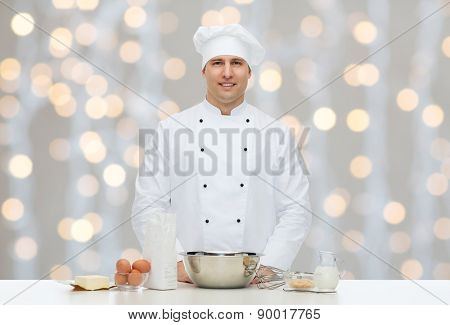cooking, profession, haute cuisine, food and people concept - happy male chef cook baking over christmas holidays lights background