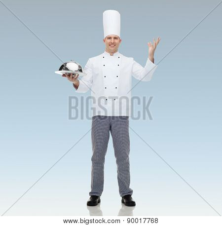 cooking, profession and people concept - happy male chef cook holding cloche  over blue background