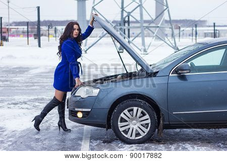 Attractive woman holding on to the hood of her car