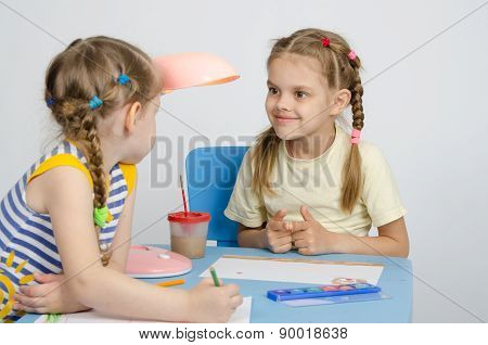 Two Girls Drawing A Table Looking At Each Other