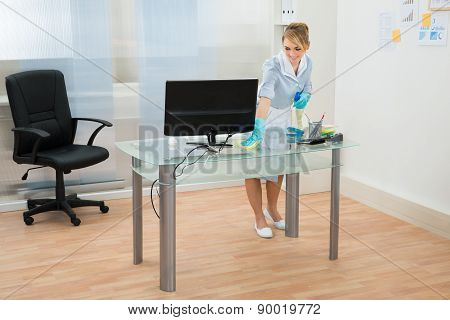 Maid Cleaning Desk In Office