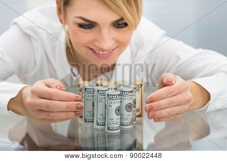 Businesswoman With Rolled Dollar Banknote