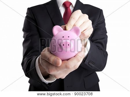 Businessman putting coin into the piggy bank isolated on white background. Clipping path included.