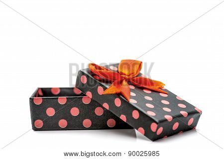Black Gift Box With Pink Dots And Orange Ribbon Isolated In White Background