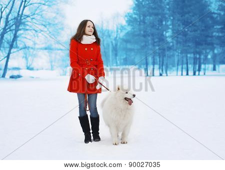 Happy Pretty Woman Walking With White Samoyed Dog Outdoors In Winter Park