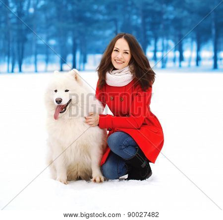 Winter, Christmas And People Concept - Happy Woman Having Fun With White Samoyed Dog Outdoors In Win