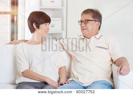 Senior couple having conversation, sitting on sofa at home. Living lifestyle of Asian family.