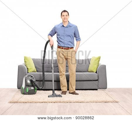 Young man posing with a vacuum cleaner in front of a modern gray sofa isolated on white background