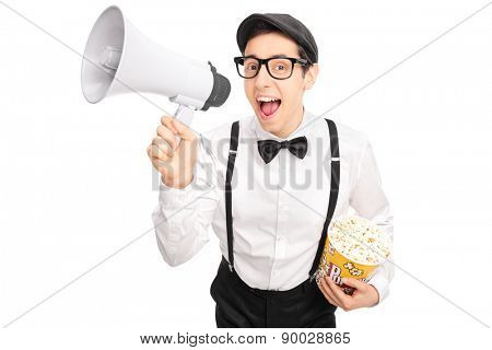 Young guy in artistic outfit holding a box of popcorn and speaking on a megaphone isolated on white background