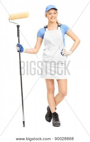 Full length portrait of a female house painter in a yellow uniform posing with a paint roller isolated on white background