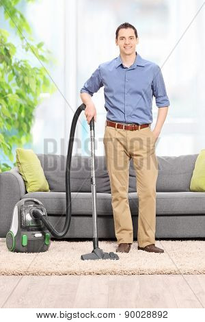 Full length portrait of a young man posing with a vacuum cleaner in front of a gray couch at home