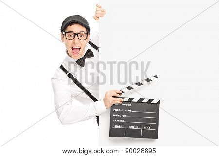 Excited movie director holding a movie clapperboard and posing behind a blank panel isolated on white background