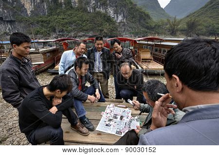 Chinese Men, Boatmen Playing Card Game Near Pier, Guangxi, China.