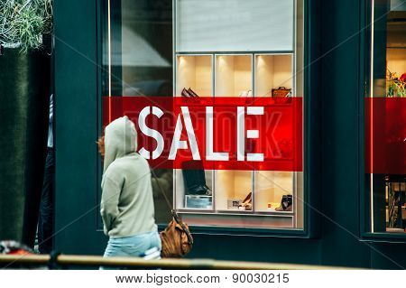 Woman Passing In Front Of Large Window Of Luxury Store