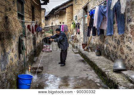 Asian Elderly Villager Pours Water From Bucket On Narrow Street.