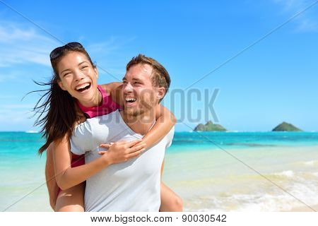 Beach couple having fun laughing on Hawaii holiday. Beautiful Asian mixed race woman piggybacking on Caucasian boyfriend on Lanikai beach, Oahu, Hawaii, USA with Mokulua Islands.
