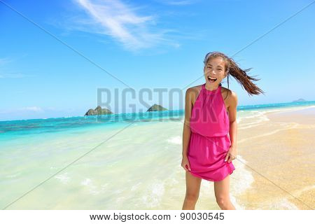 Woman having fun portrait on Hawaii Lanikai beach. Young mixed race female by water wearing pink sundress laughing during summer travel holidays on Oahu, Hawaii, USA with Mokulua Islands.