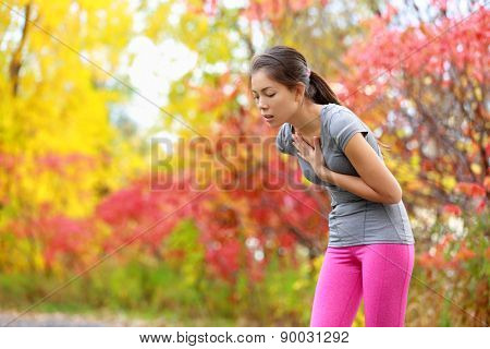 Running nausea - nauseous and sick ill runner vomiting. Running woman feeling bad about to throw up. Girl having nausea from dehydration or chest pain.