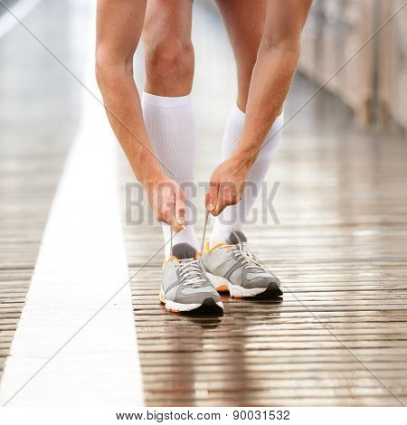 Running shoes. Man tying shoe laces. Closeup of male sport fitness runner getting ready for jogging workout outdoors path in rain in urban city setting.