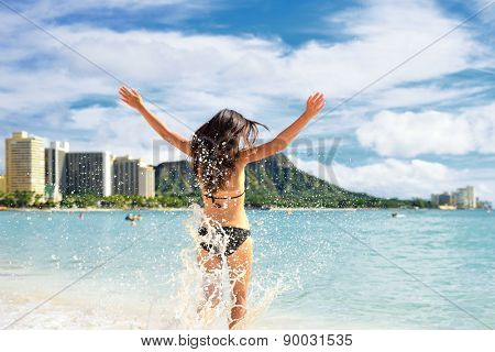 Beach fun - happy woman on Hawaii Waikiki vacation. Unrecognizable young adult from behind jumping of joy in water waves, arms up with diamond head mountain in the background, landmark of Honolulu.