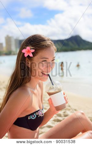 Beach woman drinking iced coffee cappuccino drink enjoying beach lifestyle smiling happy on Waikiki, Honolulu, Oahu, Hawaii, USA. Mixed race Asian Caucasian female in bikini.