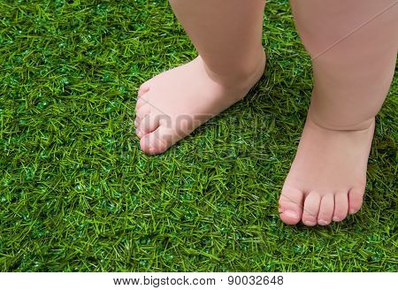 Baby bare legs standing  on green grass