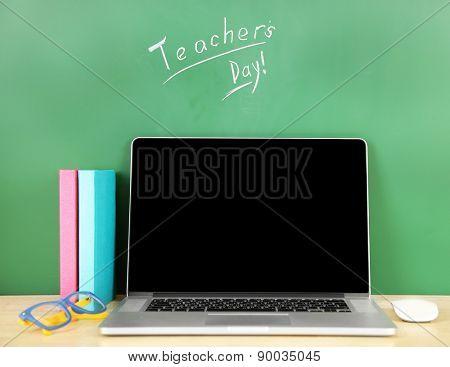 Laptop on table, on green blackboard background