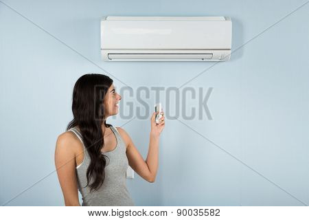 Woman With Remote Control Of Air Conditioner