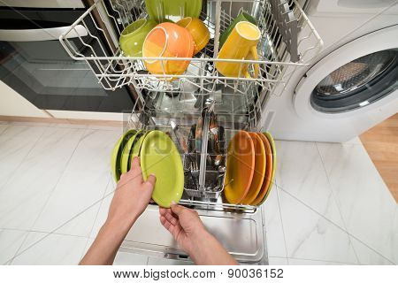 Person Hands Putting Plate In Rack