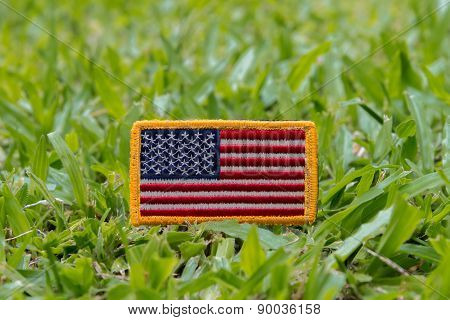 Rounded American flag patch on green grass field