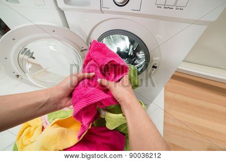 Person Hands Putting Towels Into The Washing Machine