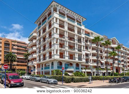 Modern residential complex under blue sky in town of Menton, France.
