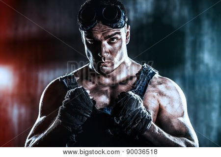 Brutal muscular dirty man expressing aggression over dark grunge background. Mining industry. World of the future, Apocalypse.