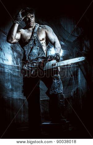 Handsome muscular man with a chainsaw over dark grunge background.