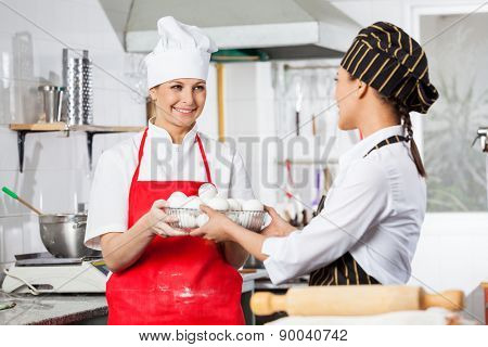 Happy female chef giving container full of eggs to colleague in commercial kitchen