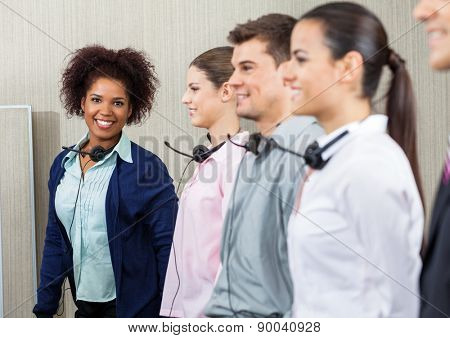 Portrait of happy female call center employee standing with team at call center