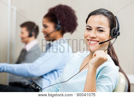 Portrait of smiling customer service representative with colleagues in background at office