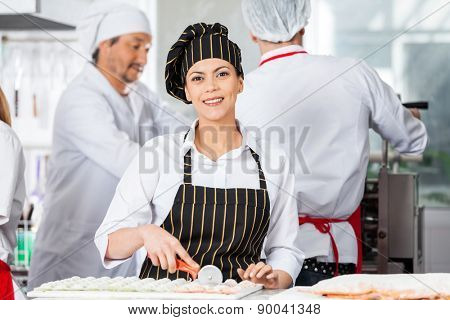 Portrait of happy female chef cutting ravioli pasta at counter with colleagues working in background at commercial kitchen
