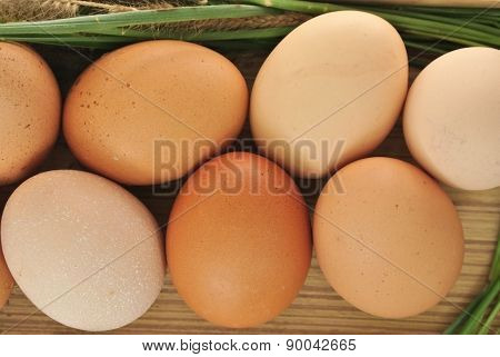 Eggs in wooden box and grass on white background
