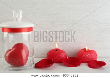 Decorative heart in glass jar on light background