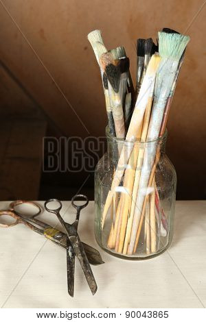 Paintbrushes in vase on wooden background